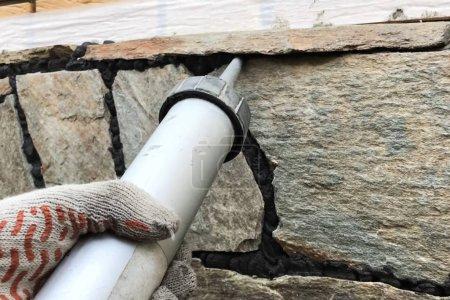 Photo pour Chanter les trous entre la pierre sauvage sur le revêtement de la fondation. Face à la fondation d'une maison - image libre de droit