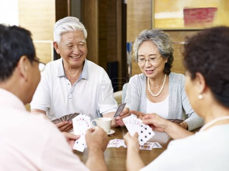 Tow senior asian couples playing cards together...