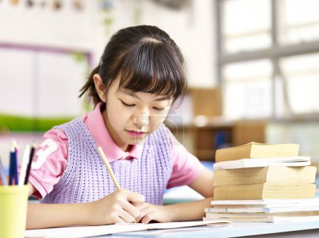 Photo for Asian elementary schoolgirl studying or doing course work in classroom. - Royalty Free Image