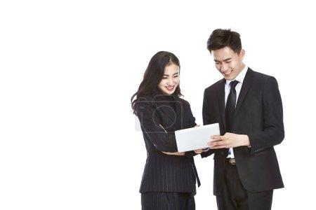 Photo pour Jeune homme d'affaires asiatique et femme d'affaires travaillant ensemble à l'aide d'une mini tablette numérique, isolé sur fond blanc . - image libre de droit
