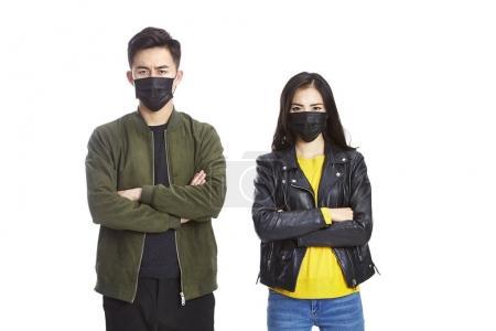 Photo pour Jeune asiatique homme et femme portant noir masque regardant caméra fronçant les sourcils, isolé sur fond blanc . - image libre de droit