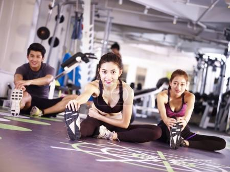 Photo for Three young asian adult people exercising in gym stretching legs. - Royalty Free Image