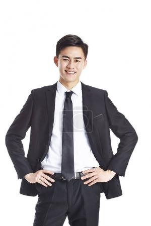 Photo for Studio portrait of a young asian business man, arms akimbo, looking at camera smiling, isolated on white background. - Royalty Free Image
