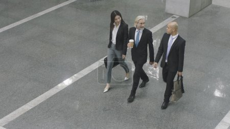 Photo for High angle view of three corporate executives talking while walking across lobby of modern office building. - Royalty Free Image