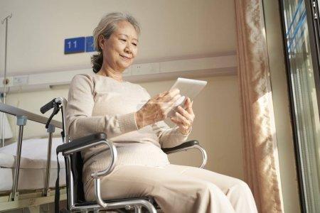 Photo pour Une femme âgée d'Asie utilisant un comprimé numérique dans une maison de soins infirmiers ou une salle d'hôpital - image libre de droit