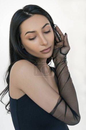 Photo pour Modèle de mode indienne sexy posant pour des photos en studio, isolé de fond blanc. Portrait d'une femme élégante et séduisante, au visage et au corps magnifiques, portant des gants élégants. Concept de beauté naturelle - image libre de droit