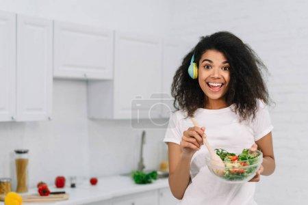 Photo pour Belle femme afro-américaine excitée cuisinant un dîner végétarien dans la cuisine. Concept de mode de vie sain. Fille émotionnelle heureuse tenant barbe avec salade fraîche, écoutant de la musique à la maison, riant - image libre de droit