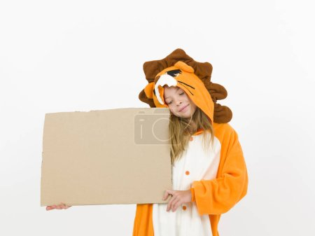 Photo pour Pretty blonde girl in cozy lion costume posing with cardboard blank banner in front of white wall - image libre de droit