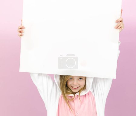 Photo for Happy pretty blonde girl in cozy rabbit costume with white sign posing in studio - Royalty Free Image