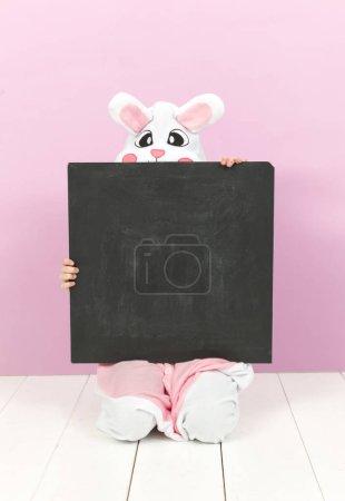 happy pretty blonde girl in cozy rabbit costume with empty blackboard posing in studio