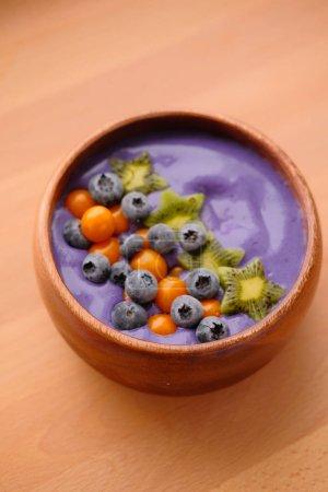 Photo pour Yogourt violet savoureux avec bleuets et kiwis en assiette - image libre de droit