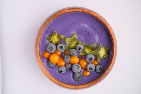 Photo for Tasty violet yogurt with blueberries and kiwi in plate - Royalty Free Image