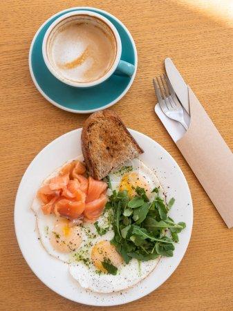 Photo pour Assiette avec œufs frits et herbes avec pain et poisson avec cappuccino tasse sur table en bois, vue de près - image libre de droit