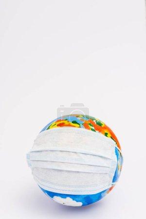 Photo pour Globe en masque médical de protection sur blanc avec espace de copie - image libre de droit