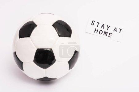 Photo pour Football près de papier avec rester à la maison lettrage sur blanc avec espace de copie - image libre de droit
