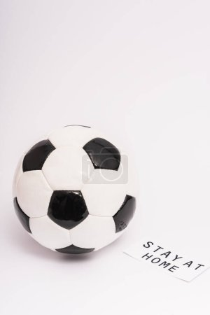 soccer ball near paper with stay at home lettering on white