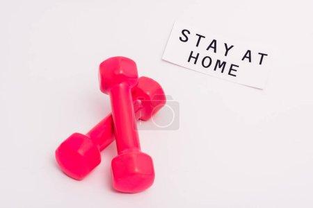 Photo pour Haltères roses près du papier avec lettrage séjour à la maison sur blanc - image libre de droit