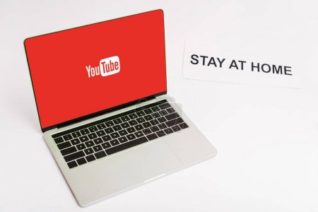 Photo pour KIEV, UKRAINE - 8 AVRIL 2020 : laptop with youtube website on screen near paper with stay at home lettering on white - image libre de droit