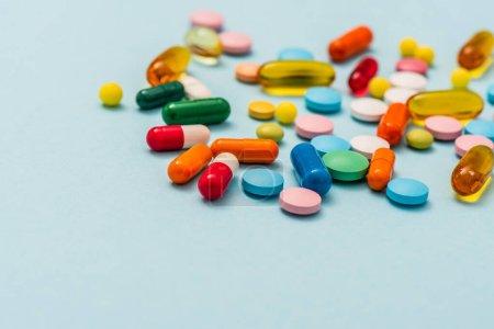 Photo pour Concentration sélective de pilules et capsules colorées sur fond bleu - image libre de droit