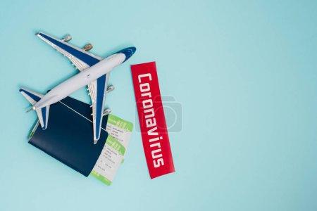 Vue du dessus du jouet près de la carte avec lettrage coronavirus et passeports avec billets d'avion sur bleu