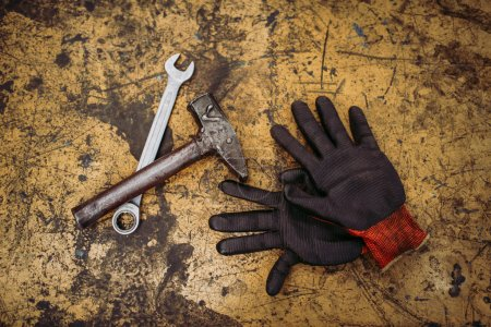 Gloves, hammer and wrench on old metal background, top view, closeup