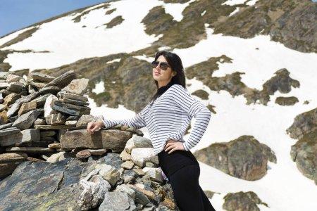 Photo pour Belle femme souriante dans des lunettes de soleil dans des rochers en plein air de montagnes arrière-plan - image libre de droit