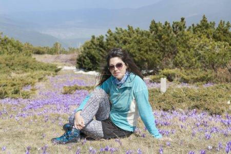 Photo pour Belle jeune femme assise dans un champ avec des fleurs sauvages - image libre de droit
