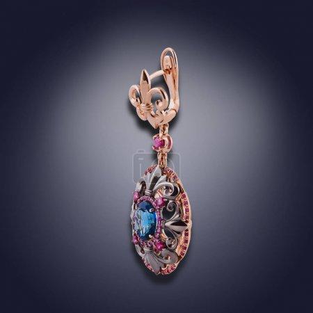 Photo pour Boucle d'oreille or et pierres précieuses de couleurs bleus et violettes pour les filles - image libre de droit
