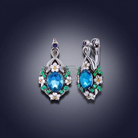 Photo pour Ensemble de boucles d'oreilles avec des motifs de fleurs et topaze bleue - image libre de droit