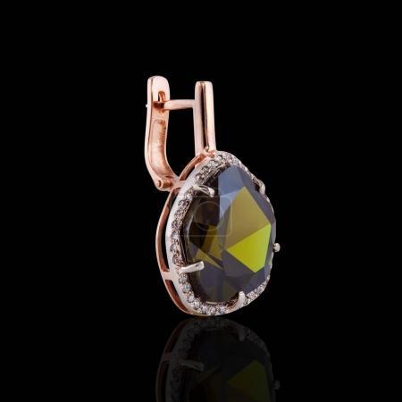 Photo pour Boucle d'oreille or avec émeraude ronde et cristaux le long des contours pour les femmes - image libre de droit