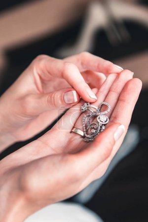 Photo pour Jeune fille tient un collier et boucles d'oreilles avec strass dans ses mains - image libre de droit