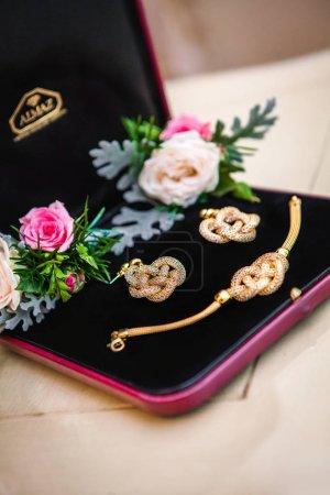 Photo pour Set de bracelet en or et fixe les boucles d'oreilles dans une boîte de velours avec des fleurs pour le don - image libre de droit