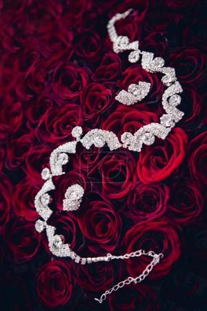 Photo pour Fixé par colliers et boucles d'oreilles fixe sur le bouquet de roses - image libre de droit