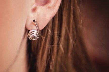 Photo pour Boucles d'oreilles or avec perles dans l'oreille de la jeune fille - image libre de droit