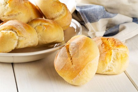 Bunch of whole, fresh baked wheat buns on plate with kitchen tow