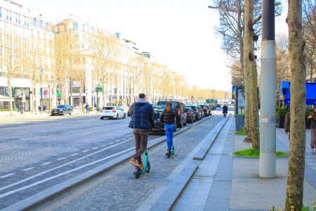 Photo pour Paris, France. 15 mars 2020. Couple faisant de la trotinette électrique sur l'avenue des Champs-Élysées. Une alternative écologique pour les transports, contre la pollution . - image libre de droit