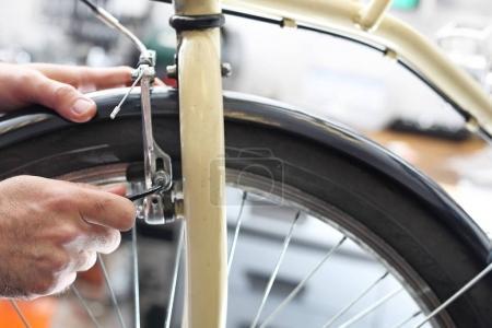 Bike workshop, mechanic exchanges spokes.