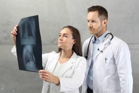 Doctors are looking at the patient's x-ray picture.