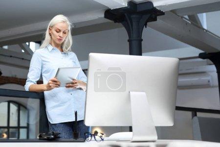 Foto de Trámites. El empleado corporativo relaja leyendo la tableta - Imagen libre de derechos
