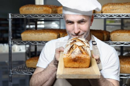 Photo for Rye bread. A handsome baker with a loaf of fresh bread standing in the bakery. - Royalty Free Image