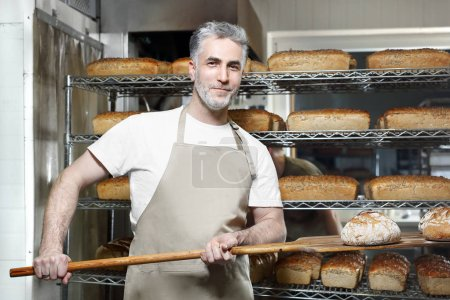 Photo for Baker working in the bakery. The baker in the bakery takes out the fresh bread from the oven - Royalty Free Image