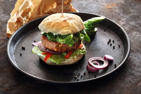 Vegan burger. Roll with vegetable cutlet and vegetables served on a black plate