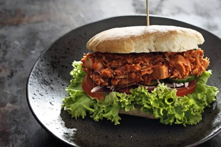 Sandwich with grilled vegetable cutlet. Tasty sandwich with buns with the addition of a grilled lettuce, tomato and onion cutlet served on a plate.