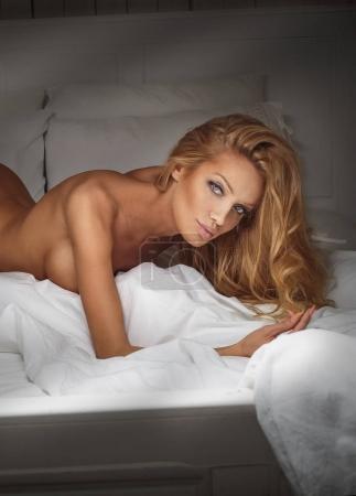 Blonde woman posing in hotel room.