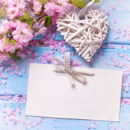 Photo for Fresh pink  sakura flowers,  decorative heart and empty tag on blue wooden planks. Selective focus. Place for text. Flat lay. Top view. Shabby chic. Square image - Royalty Free Image