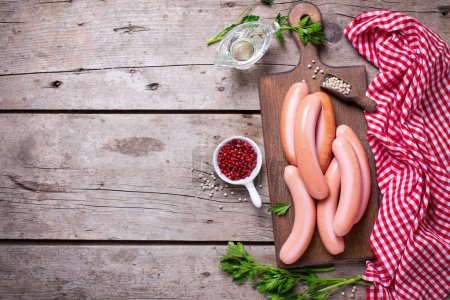 Sausages on board  with herb and spices on vintage...