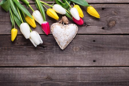 Decorative heart and bright spring tulip flowers