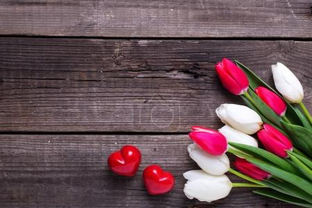 Two red decorative hearts and bright spring tulip flowers