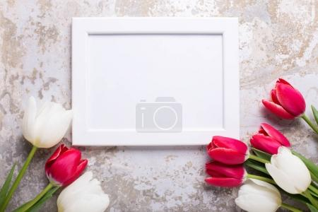 Empty photo frame and tulips