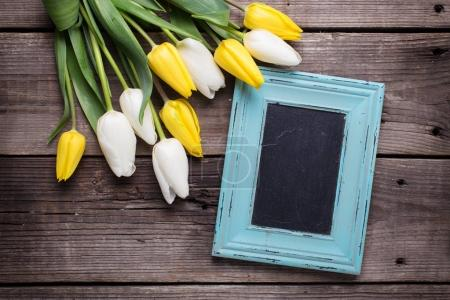 Empty blue frame and yellow and white tulips flowers  on  vintage wooden background. Selective focus. Place for text.